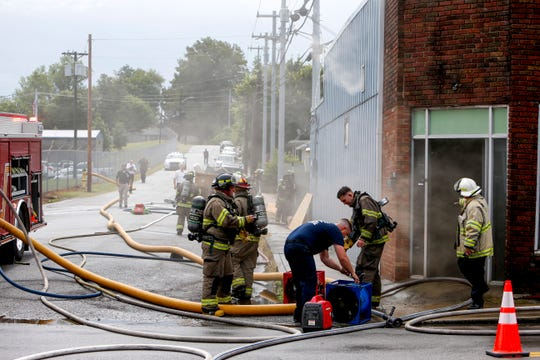 Clarksville firefighters coordinate monitoring the remains of a structure fire and put away gear after putting out the flames at 213 South 10th St, formerly Law's Market in Clarksville, Tenn., on Thursday, June 20, 2019.