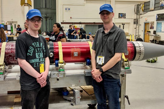 Zach Hill, left, and Zach Givens pose with the rocket that will carry their experiment to space.