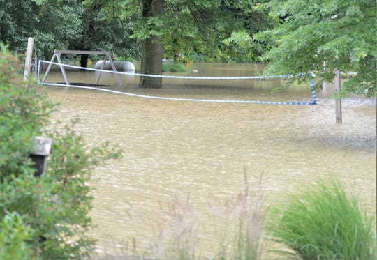 A volleyball net in the backyard of one of the homes located near County Road 16 and Township Road 13 on Thursday afternoon. Several homes are still not accessible, as crews were pumping water out of the housing complex.