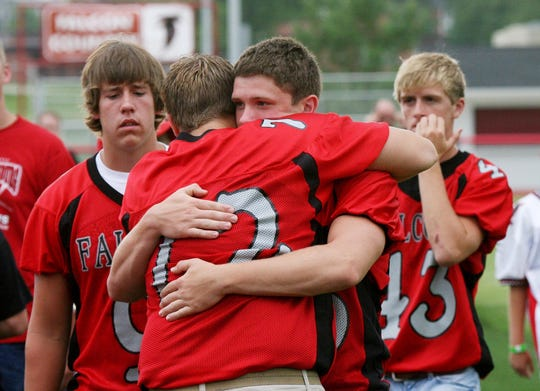 Aplington-Parkersburg students and teammates hug each other in 2009 during a vigil following Ed Thomas' murder.