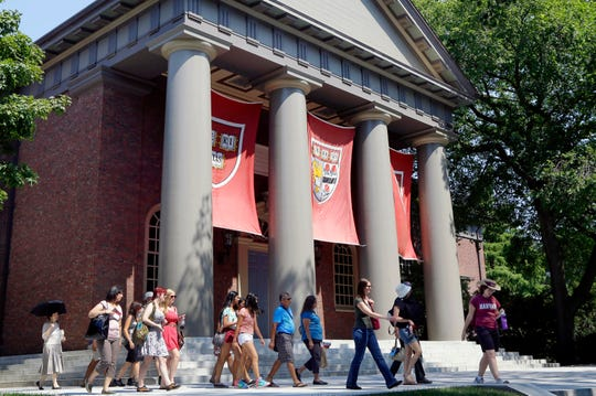 A tour group walks through the campus of Harvard University in Cambridge, Mass.