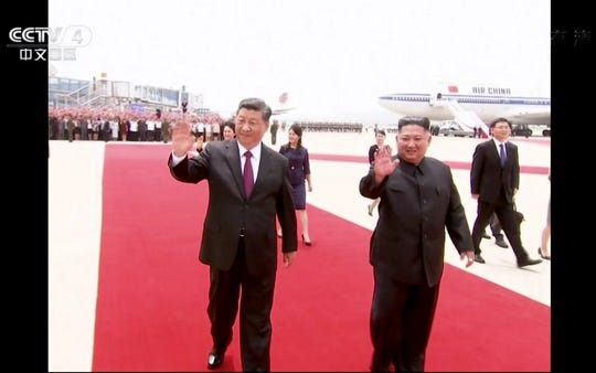 In this image taken from a video footage run by China's CCTV, Chinese President Xi Jinping, left, and North Korean leader Kim Jong Un wave as President Xi arrived at an airport in Pyongyang, North Korea, Thursday, June 20, 2019.
