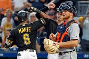 Pittsburgh Pirates' Starling Marte (6) celebrates with Bryan Reynolds, back right, near Detroit Tigers catcher John Hicks after hitting a two-run home run off Tigers relief pitcher Nick Ramirez during the fifth inning.