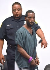 Alleged serial killer Deangelo Martin is handcuffed as he is escorted into a Wayne County courtroom