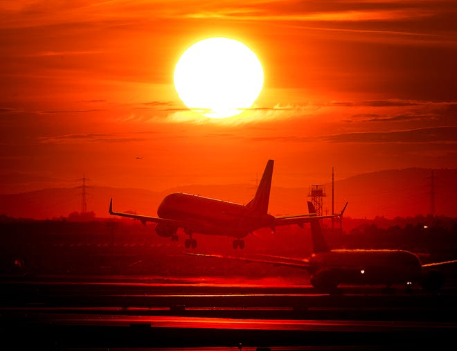An aircraft lands at the international airport in Frankfurt, Germany, as the sun sets.