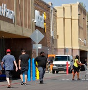 In this June 3, 2019, photo, shoppers enter and exit a Walmart in Tempe, Ariz. Walmart Inc. ended a seven-year investigation by the U.S. government over payments made to fast-track store openings in several countries by agreeing to pay more than $282 million in penalties.