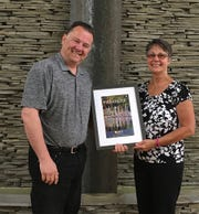 "Watkins Glen resident Teresa Schimizzi is honored by Watkins Glen Chamber of Commerce Tourism & Marketing Manager Paul Thomas for her colorful photo of sailboats in the Seneca Lake harbor in Watkins Glen that was selected for the cover of the 2019 Watkins Glen and Schuyler County Travel Guide. Schimizzi took the photograph from her kayak. ""We were all happily surprised at how many high-quality, professional-looking photos were submitted for our photo contest in 2018,"" Chamber President and CEO Rebekah Carroll said. ""It is a testament to our creative residents and visitors alike that they were able to submit so many incredible images from throughout our many beautiful communities and sights."""