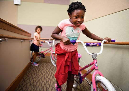 Caze Elementary school student, Katura June rolls away her new bike at the 14th annual bike give away for middle and elementary school students participating in the Ivy Tech Community College Public Safety Academy Thursday, June 20, 2019.