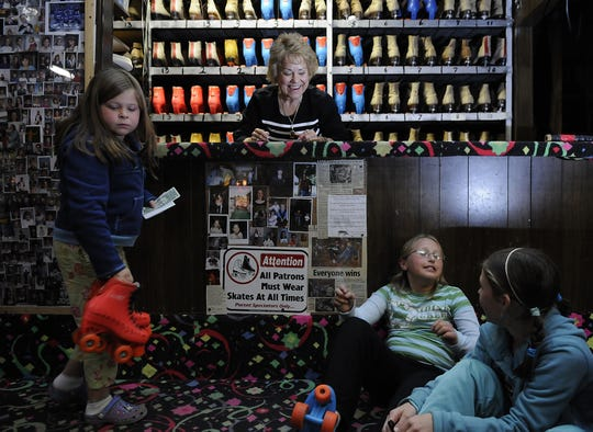 Mary Dollar, owner of Rola-Rena in Ashwaubenon, shares a laugh with a group of kids while working the skate counter in 2008. She got to know three generations of kids during her 47 years in the business.