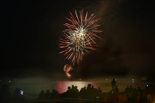 Guests watch fireworks over lake Michigan from Alclam Park during a  Fourth of July celebration in Baileys Harbor.