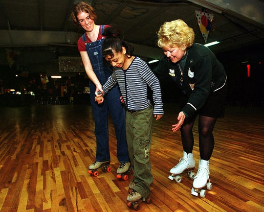 Seven-year-old Tiffany Halstead,  center, roller skates for the first time with help from Rola-Rena owner Mary Dollar, right, in 2000. Dollar has taught hundreds of kids how to skate.