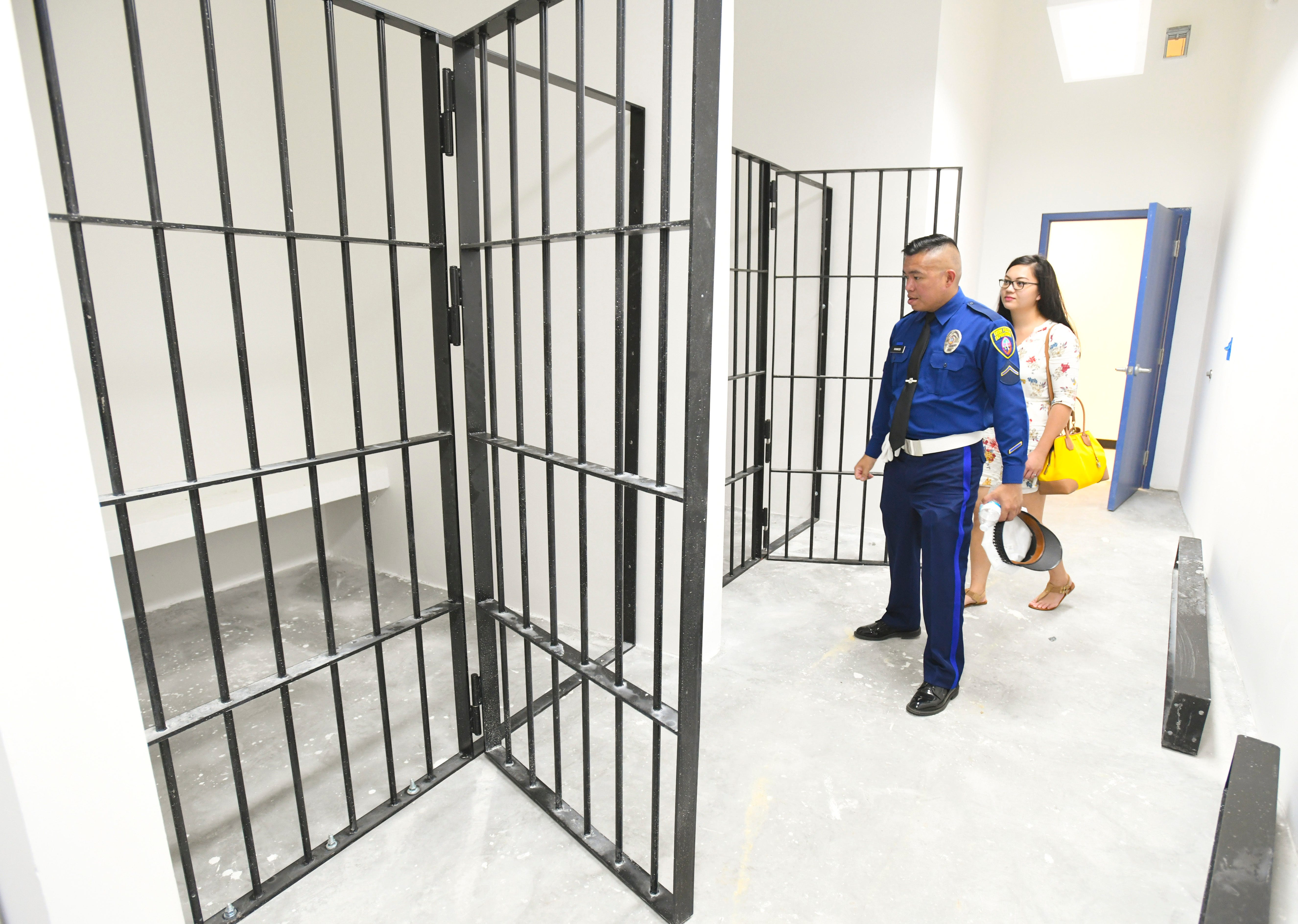 Police officer M.A. Ramos and a guest check out the holding cells still under construction within the Guam Police Department's new Central Precinct Command in Sinajana on Thursday, June 20, 2019. A ribbon cutting ceremony was held earlier to celebrate the opening of the facility.