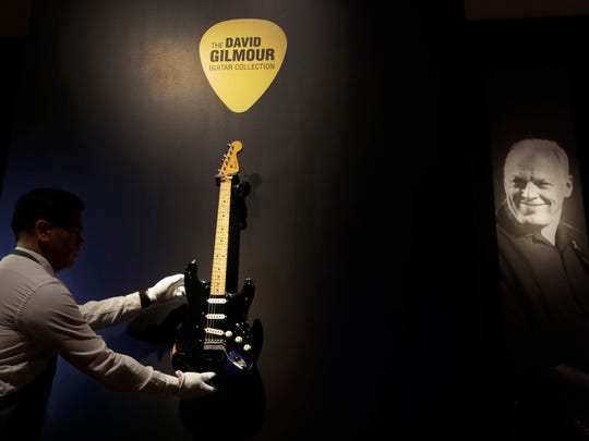 """A technician arranges """"The Black Strat"""" from the collection of David Gilmour during an March 27 open house at Christie's auction rooms in London."""