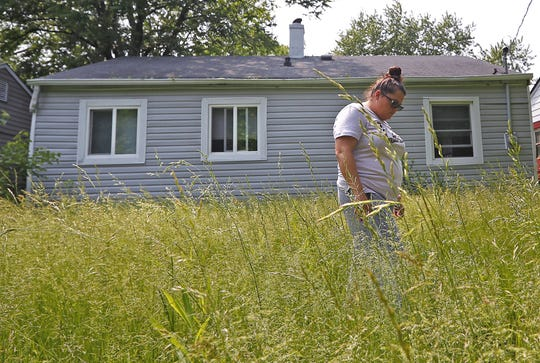 April Blythe walks through tall grass and weeds at a rental property managed by one of Bert Whalen's companies, Freeport Invest. She said the inside of the home was filled with mold and it had electrical problem. Blythe said the company moved her into another home it manages after learning she had been in contact with IndyStar.