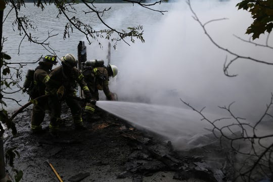 Firefighters extinguish a fire near Maplewood Point Road.