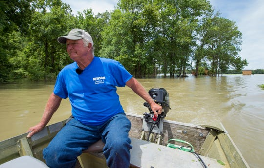 David Sellers of Holly Bluff guides his boat along the Sunflower River and unrecognizable Holly Bluff farmland hidden by floodwaters.
