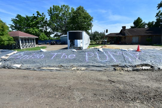 "A clear message to ""finish the pumps"" is painted on tarp covering a levee protecting houses across from farmland flooded by backwaters in Holly Bluff. Wednesday, June 12, 2019."