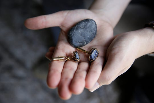 Dane Shikman holds a rock from the beach where the ashes of his mother, Elizabeth Gaunt, were scattered in Ireland along with a pair of cufflinks she had made for him as he sits at his home in San Francisco on Friday, April 19, 2019. His mother, who had a history of mental health and substance abuse problems, killed herself at the Lake County, Calif, jail in 2015, after she repeatedly cried for help. Her son's wrongful death lawsuit resulted in a $2 million settlement. (AP Photo/Eric Risberg)