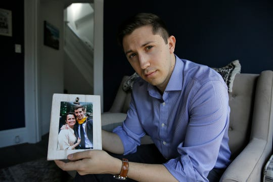 Dane Shikman holds a photograph showing him with his mother, Elizabeth Gaunt, at his home in San Francisco on Friday, April 19, 2019. Gaunt, a former social worker with a history of mental health and substance abuse problems,  killed herself in 2015 in the Lake County Jail in northern California. Her son's wrongful death lawsuit resulted in a $2 million settlement. Changes also were made at the jail. (AP Photo/Eric Risberg)