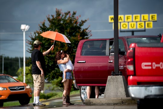 People shield themselves from the rain at a McDonald's on Strawberry Plains Pike in Knoxville on Thursday, June 20, 2019.