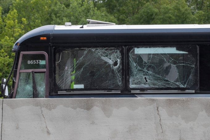 A Greyhound bus sits with windows broken after it collided with a passenger vehicle that was traveling north on the southbound side of I-65 on Thursday between Bonnieville and Munfordville, Ky. June 20, 2019