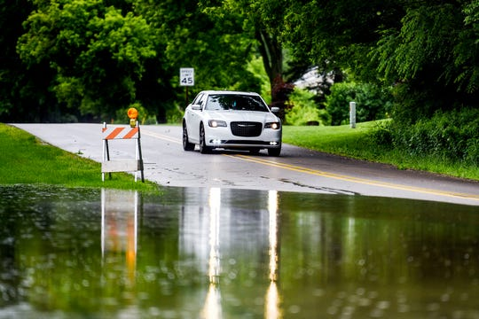 A vehicle approaches a partially flooded portion of Jolly Road at the intersection of Kensington Circle on Thursday, June 20, 2019, in Lansing. Steady rain over the night Wednesday and into Thursday has caused some area roads to close.