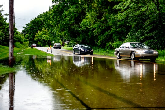 Vehicles pass by a partially flooded portion of Jolly Road at the intersection of Kensington Circle on Thursday, June 20, 2019, in Lansing. Steady rain over the night Wednesday and into Thursday has caused some area roads to close.
