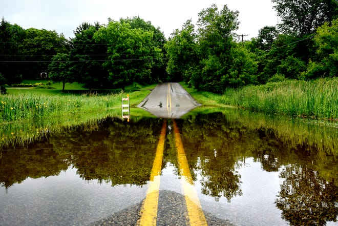 Water completely covers a low spot on Hart Highway east of Creyts Road on Thursday, June 20, 2019, in Lansing. Steady rain over the night Wednesday and into Thursday has caused some area roads to close.