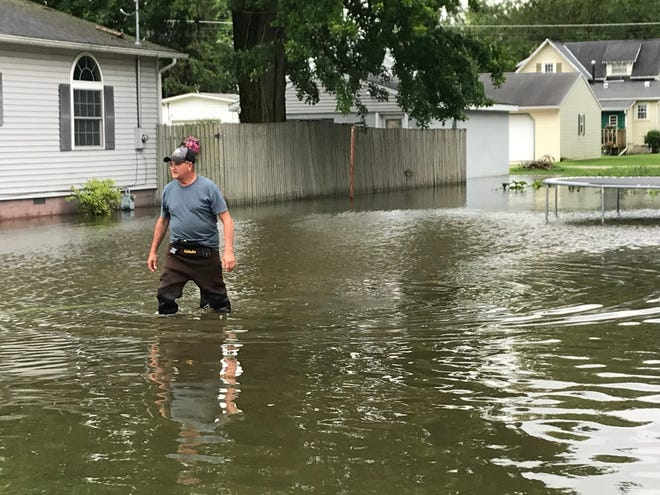 Jim Wallace wades through standing water in the empty lot beside the house his son lives in in Prospect. He was trying to pump the water out of the lot Thursday.