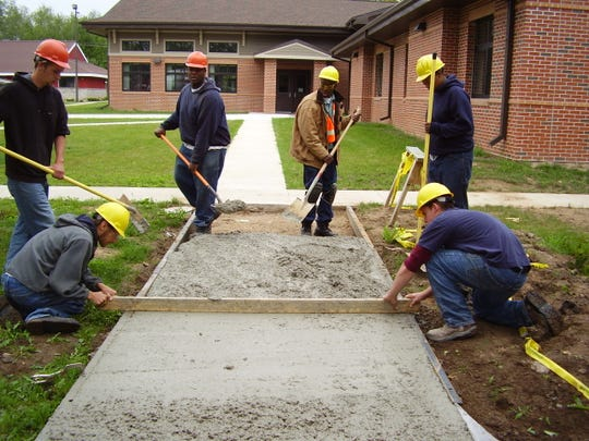 Blackwell students smooth concrete for a new sidewalk outside the center.