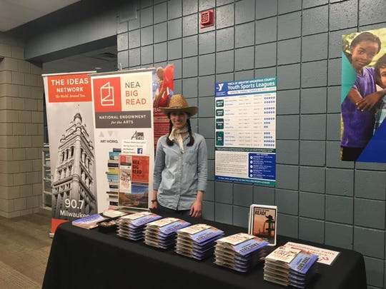 """Menomonee Falls Public Library children's librarian Amanda Caivano is distributing Charles Portis' book """"True Grit"""" at the 2019 Tri County YMCA kickoff event in Menomonee Falls for the NEA Big Read. The library received a $15,000 grant and will focus on """"Station Eleven"""" by Emily St. John Mandel in February and March 2020."""