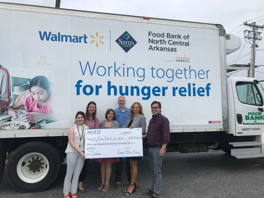 Arvest Bank associates (from left) Michaela West, Jaysa Carnal, Adrienne Blackwell, Kyle Davidson and Sally Gilbert present Jeff Quick, CEO of the Food Bank of NCA, with a donation as a result of the bank's ninth annual Million Meals campaign to reduce food insecurity locally.