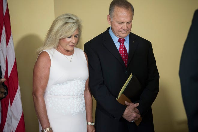 Former Alabama Chief Justice Roy Moore and his wife, Kayla, bow their heads in prayer before he announces his senate campaign in downtown Montgomery, Ala. on Thursday, June 20, 2019.