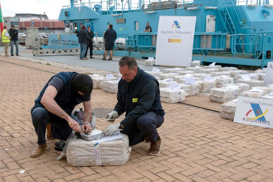 "Spanish customs officers check a pack of cocaine in the port of Vigo after seizing the vessel ""Gure Leire"" carrying 2500 kg of cocaine, on June 3, 2019. (Photo by MIGUEL RIOPA / AFP)        (Photo credit should read MIGUEL RIOPA/AFP/Getty Images)"