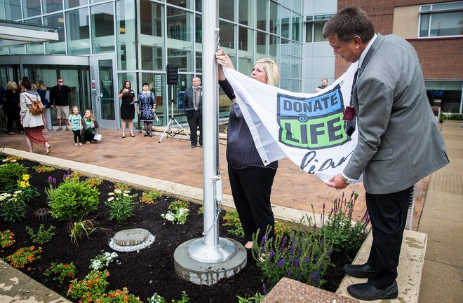 Hospital staff, donors and recipients gathered for a flag pole ceremony honoring organ donation at IU Health Ball Memorial Hospital's South Tower Thursday afternoon.