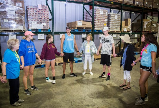 Union Chapel's SERVE Week volunteers gather for a prayer circle at the end of a shift at Second Harvest Food Bank Thursday afternoon.