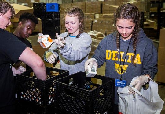 Union Chapel's SERVE Week volunteers sort through orange juice boxes for Second Harvest Food Bank Thursday afternoon.