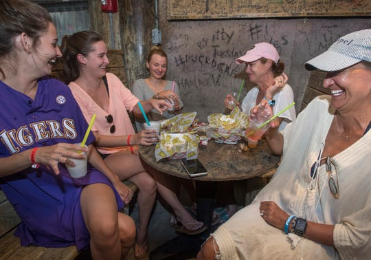 Amelia Talbot, from left, Addison Talbot, Wlissa Nunnally, Christina Virgets and Patricia Talbot, of Baton Rouge, La., enjoy themselves at the Flora-Bama Lounge in Perdido Key, Fla., on Wednesday, June 19, 2019.