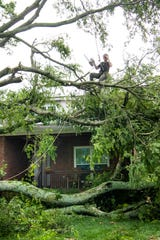 Workers begin to clear the fallen tree blocking Stacy and Jason Faries' house after severe storms in the Wades Grove neighborhood Thursday, June 20, 2019, in Spring Hill, Tenn.