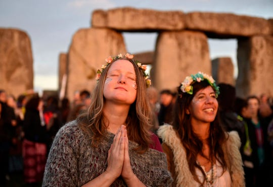 People gather to see the sun rise at the ancient stone circle Stonehenge, during the Summer Solstice, the longest day of the year, in Wiltshire, United Kingdom, Tuesday June 21, 2016.  (Andrew Matthews/PA via AP) UNITED KINGDOM OUT, NO SALES, NO ARCHIVES
