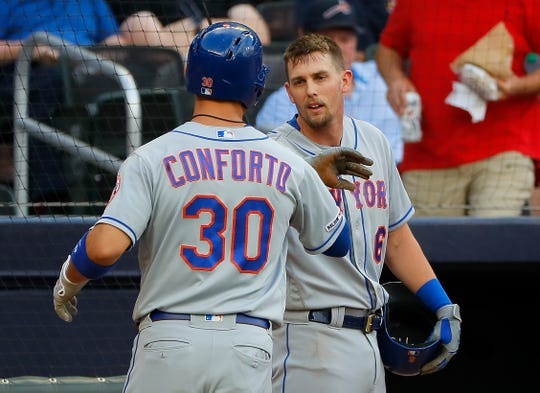 Jeff McNeil, facing, of the New York Mets reacts with Michael Conforto after he scored off his ground out in the first inning against the Atlanta Braves at SunTrust Park on June 19, 2019 in Atlanta, Georgia.