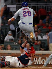 J.D. Davis #28 of the New York Mets is tagged out at home as he leaps over Tyler Flowers #25 of the Atlanta Braves in the sixth inning at SunTrust Park on June 19, 2019 in Atlanta, Georgia.