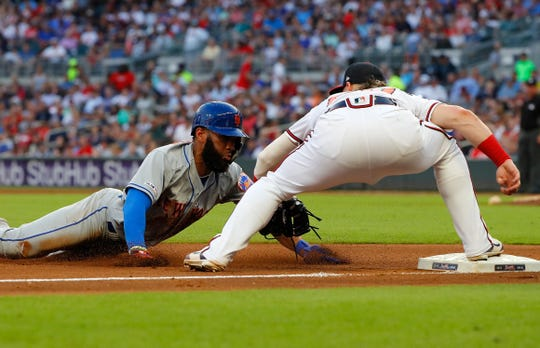 Josh Donaldson #20 of the Atlanta Braves tags out Amed Rosario #1 of the New York Mets after he hit a RBI double but attempted to take third base in the fourth inning at SunTrust Park on June 19, 2019 in Atlanta, Georgia.