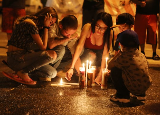 """Family members and close friends of Francisco """"Paco"""" Tarin, who was killed early Monday morning in a shootout with police, gather Thursday evening at the place he died for a candle ceremony."""