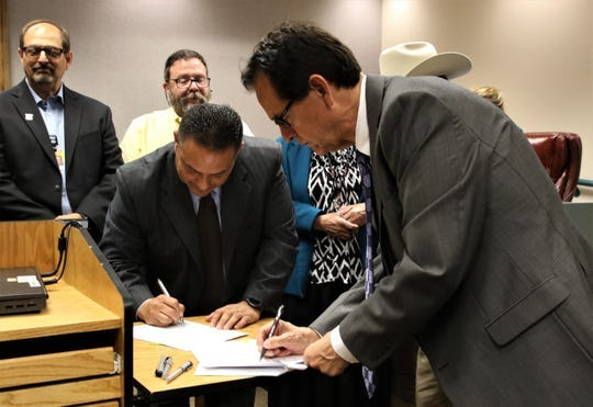 New Mexico Department of Finance and Administration Local Government Division Director Donnie Quintana, center, and San Juan County Commission Chairman Jack Fortner sign a grant agreement for a film production facility May 21 during the San Juan County Commission meeting in Aztec.