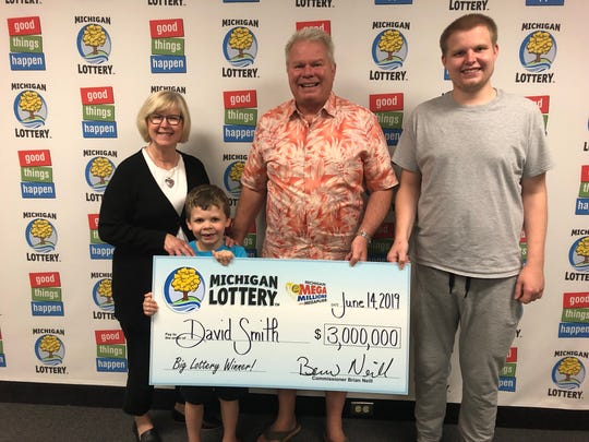 Dave and Kris Smith of Farmington Hills, with their son, Mike, and grandson, Micah, at Michigan Lottery headquarters after winning Mega Millions.
