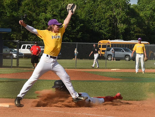 St. Landry Bank first baseman Seth Broussard stretches to grab a high throw as a runner dives underneath him Tuesday afternoon in a game against the Southland Hogs. The Indians won the game, 5-2, and then defeated the Opelousas General Health System Warriors, 13-4, in the second game of an American Legion doubleheader.