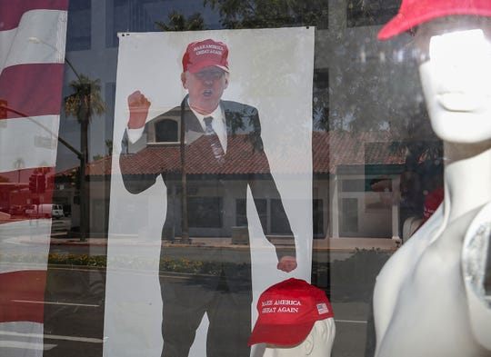 Trump posters and mannequins wearing MAGA hats adorn a window display of Denise Roberge Jewelry and Art Gallery on El Paseo Drive in Palm Desert, June 20, 2019.