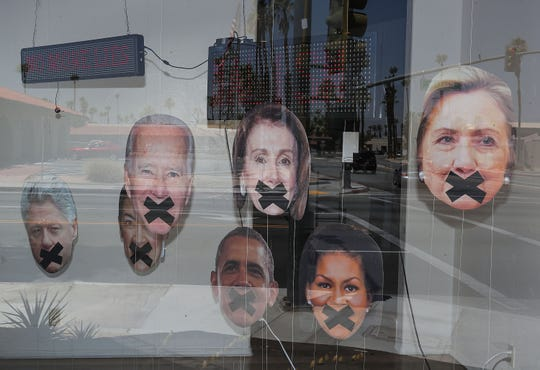 The faces of liberal politicians with their mouths taped shut are in the window display of Denise Roberge Jewelry and Art Gallery on El Paseo Drive in Palm Desert, June 20, 2019.
