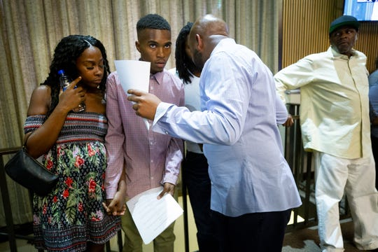 The Rev. Jarrett Maupin, right, speaks to Iesha Harper and her fiance, Dravon Ames, during a Phoenix City Council meeting. The couple were filmed in a viral video showing Phoenix police officers pointing guns at them after an alleged shoplifting incident.